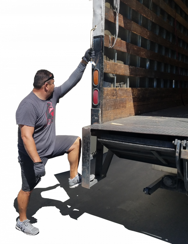 Worker gripping on grab handle installed on back of semi truck